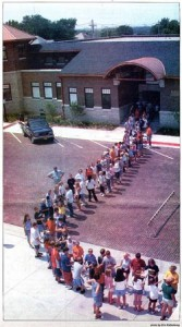people forming a line to pass book from old library to new building